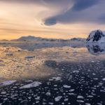 Icebergs-y-atardecer-reflejado-en-el-agua-en-Lemaire-Strait,-Antarctica