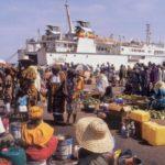Gente en el puerto y Le Joola al fondo